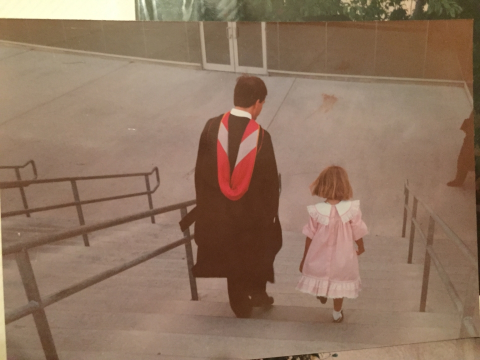 An old photo from behind of a man in a graduation gown, outside, walking down cement stairs beside a little girl in a frilly pink dress.