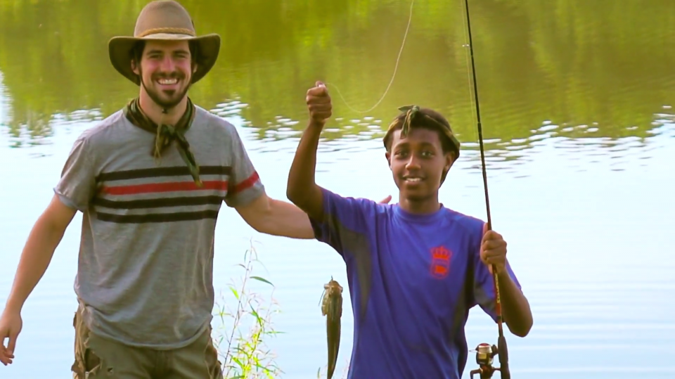 A man in his thirties, smiling, wearing a grey shirt, wide brimmed hat, and a beard, standing next to a teenage boy in a purple shirt, smiling, holding a fishing rod and fish, in front of a lake.