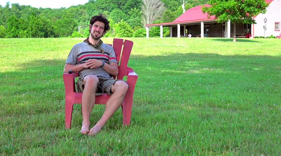A man in his thirties, wearing a gray shirt and beige shorts, sitting in a red lawn chair, in a field, with a large cottage in the background.