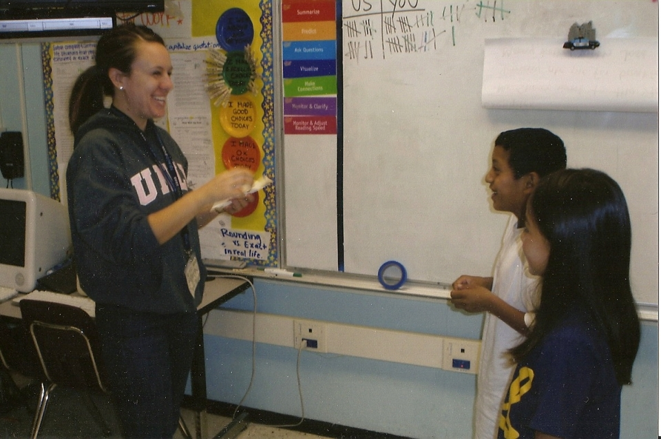 A woman in her twenties with her hair in a pony tail, wearing a grey sweatshirt and jeans stands in front of a whiteboard in a classroom smiling at two young students.