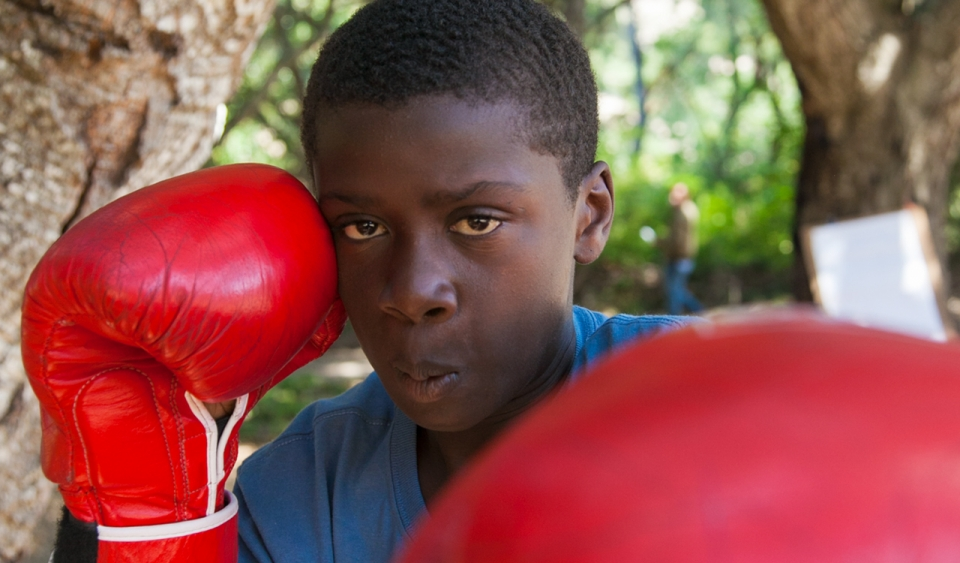 A kid boxing with red gloves
