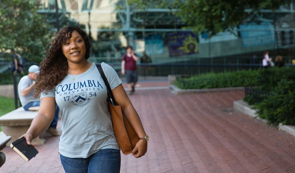 A woman wearing a Columbia shirt walking