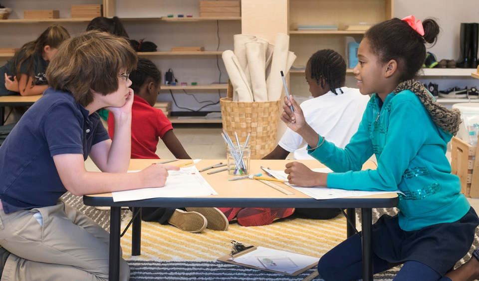 Two students work together at a table