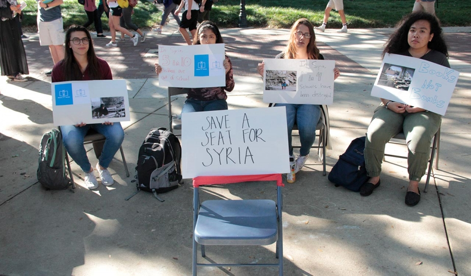 Students sitting holding signs