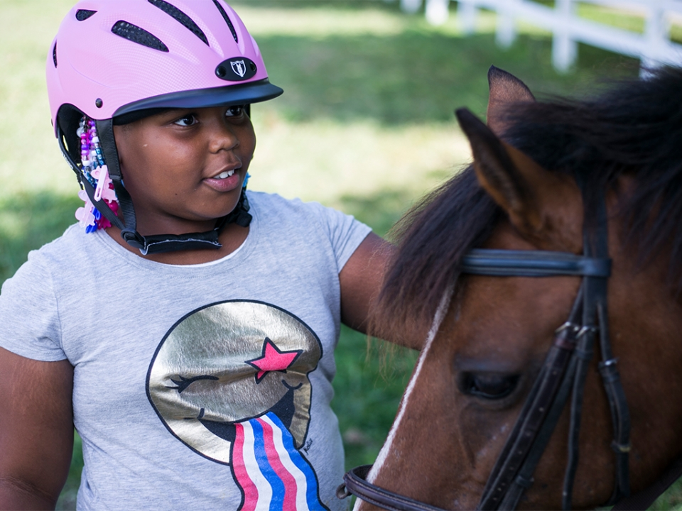 A young girl pets a horse.