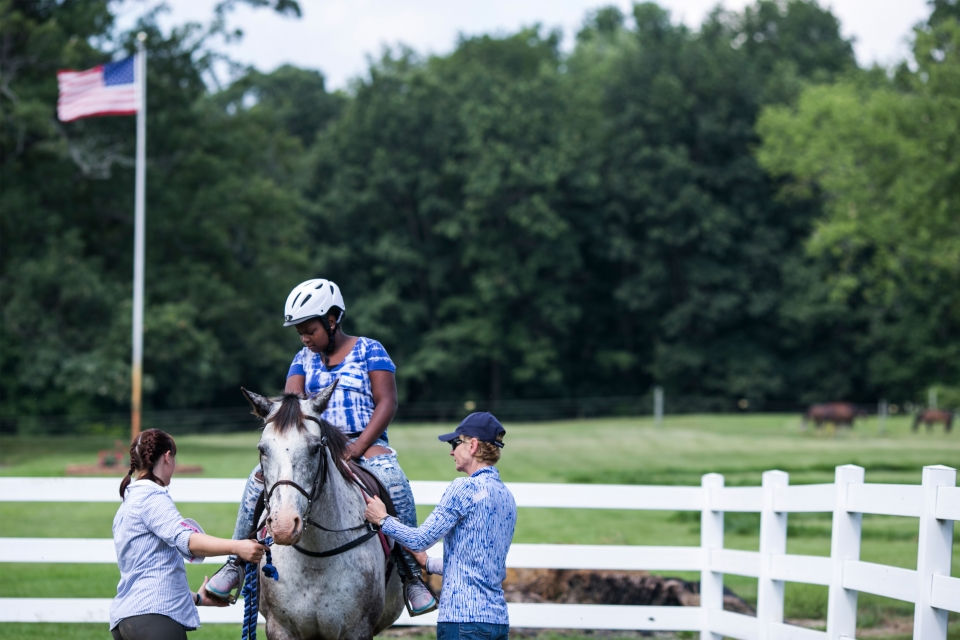 A young girl on a horse listening to directions from the instructors.