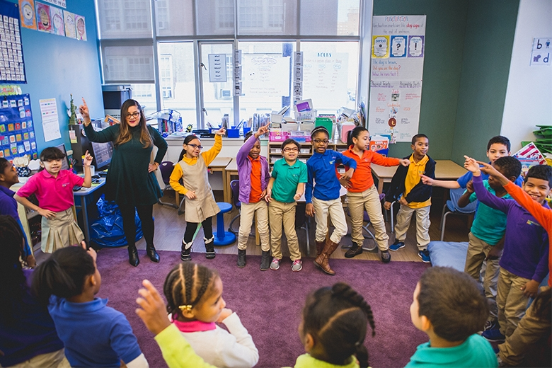 A second grade class and their teacher dances during their morning meeting.