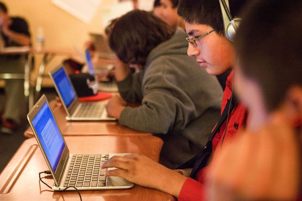 A group of middle-school students, working at laptops.