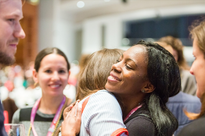 A group of Teach For America alumni, hugging.