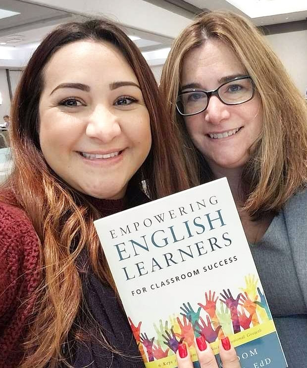 Former student and her teacher holding a book.