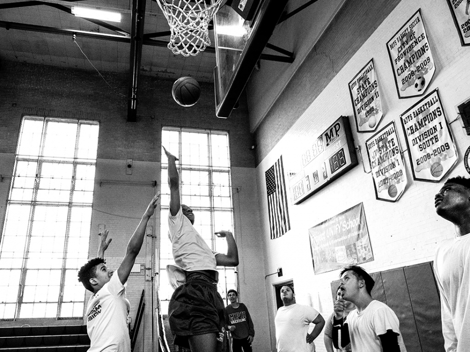 Two young men play basketball
