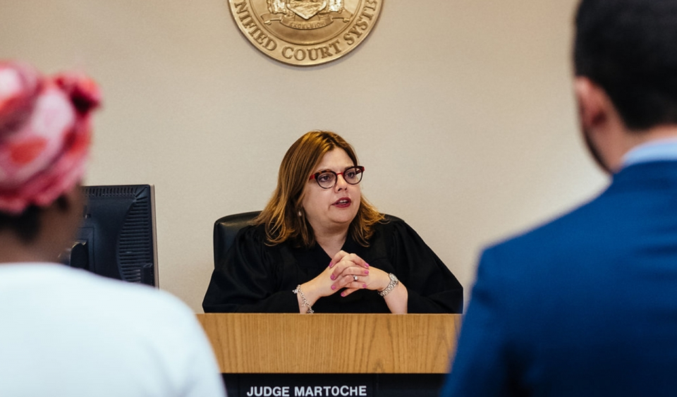 A judge sits in court while two people stand and face her