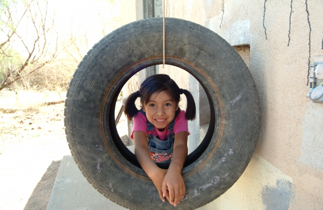 An elementary school girl with straight black hair in pigtails lies on her elbows inside a suspended tire swing in a yard, smiling.