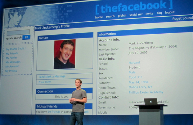 A young man with short blond hair and a blue shirt giving a presentation in front of a large screen showing the first version of Facebook and Mark Zuckerberg's profile.