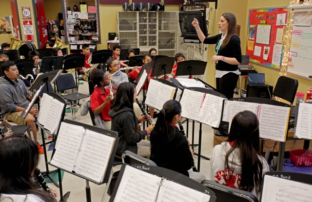 A young female teacher with straight brown hair conducting a middle-school music class.