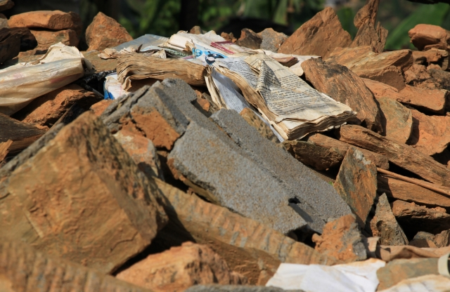 A waterlogged book lays on a pile of brown brick rubble.