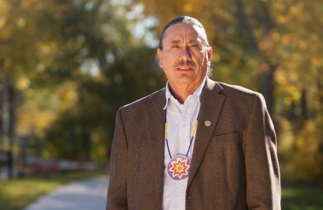 A tall middle-aged man wearing a suit jacket and a traditional Native American necklace stands in the middle of a sidewalk, with a row of trees behind him.