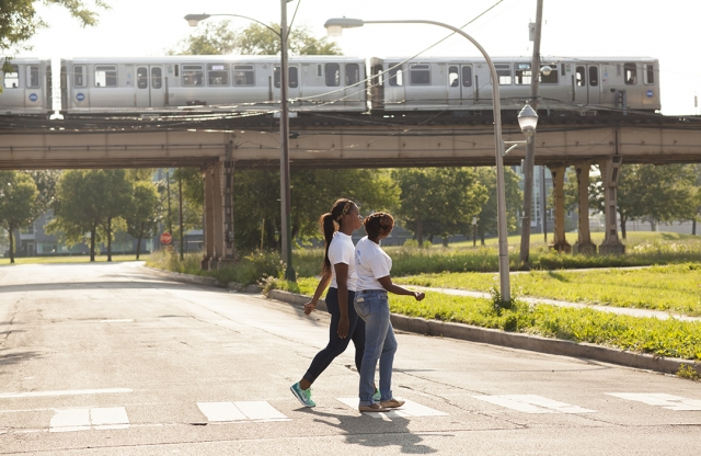 Two young women in white shirts cross the street, with a train on raised tracks visible in the background.