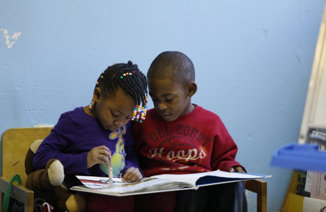 An elementary school-aged girl with curly brown braided hair sitting on a couch reading a book with an elementary-school-aged boy with a shaved head and a red t-shirt.