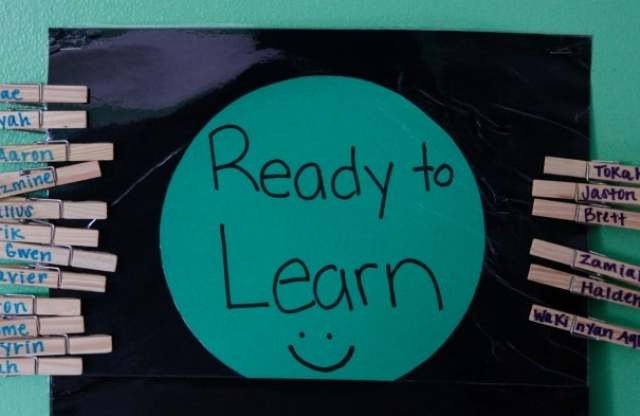 "A black shiny piece of paper with a green circle in the middle with the words ""Ready to Learn"" and a smiley face written in black maker, hanging on a green wall, with many wooden clothes pins with various names on them."