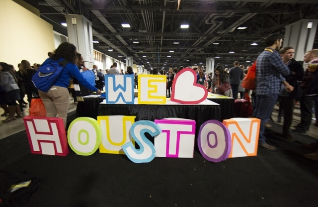 "Colorful, large cut out foam letters on and in front of table with a black skirt that spell ""We (heart) Houston"" at crowded convention hall."