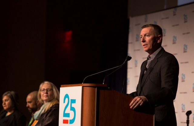 "An older gentleman with a crew cut stands behind a podium with a sign saying ""25 Years"" on it speaking to an audience while other guests on stage sit and listen."