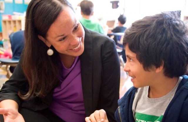 A young female teacher with long brown hair wearing a black jacket and purple shirt holding her right hand out and a elementary school boy with dark brown hair in a blue sweater look at each other, smiling, while they talk in class.