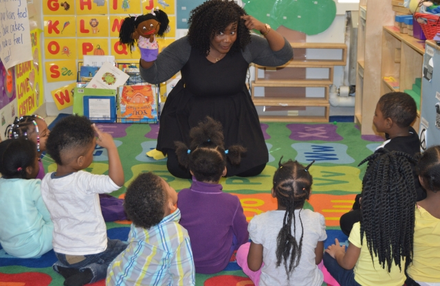 A young female teacher with curly black hair smiles as she gives a puppet show to her elementary students.