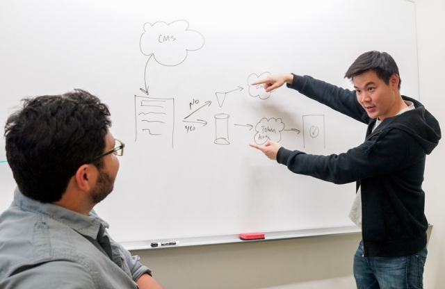 A young man with short straight black hair, wearing a black sweater, points to a whiteboard to explain a process to his colleague in a gray shirt and beard.