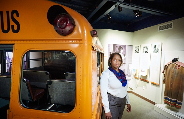 A woman stands next to a bus at the Levin Museum of the New South