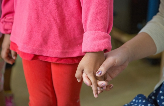 A student holds hands with her teacher.