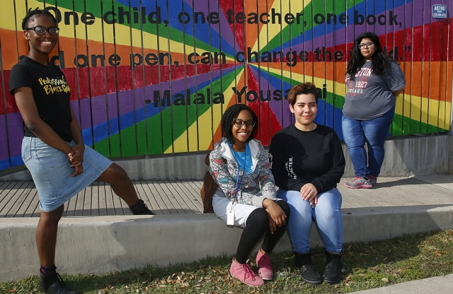 Four girls sitting in front of a mural