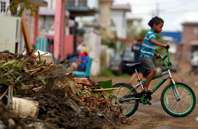 A young boy rides his bicycle through Puerto Rico.