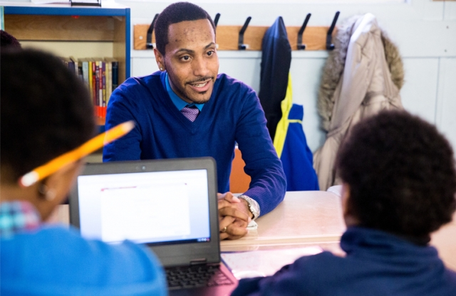 A black male Teach For America teacher working with students.