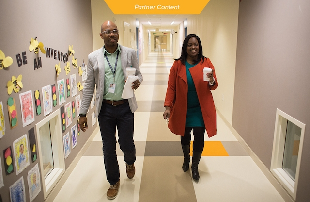 Two TFA alumni walking down a school hallway.