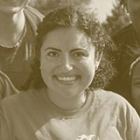 A sepia shot of a young woman with very curly chin-length dark brown hair parted on the left and pulled back, smiling and wearing a t-shirt in front of some friends.