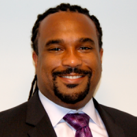 A middle-aged man with a goatee and tied back dreadlocks, wearing a black suit with a purple tie.