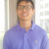 Head shot of a young man with short black hair and black framed glasses smiling in an office, wearing a light purple polo shirt.