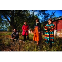Three women and a young man in Native American dress posed in a line in a field in front of an orange house.