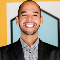 Headshot of a smiling young adult male in a suit jacket, against a bright yellow background.