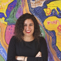 A smiling woman with curly brown hair in her thirties, wearing a black shirt and sweater, standing, with her arms crossed, in front of a colorful mural.