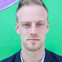 Head shot of a man in his thirties, with close cut blond hair and blue eyes, wearing a blue blazer, in front of a green wall.