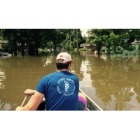 A man rows a canoe down a flooded street in Baton Rouge