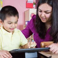 A young woman with long wavy dark brown hair leans over a pre-school student using an iPad to learn.