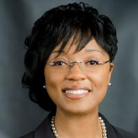 A middle-aged woman with chin-length black hair and bangs styled straight and in curls, smiling, wearing frameless glasses, pearl earrings, a pearl necklace, and a black blazer.