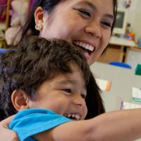 An extreme close shot of a pre-school aged boy with wild curly brown hair playing, leaning on a young female teacher with long straight black hair wearing diamond earrings, and smiling.