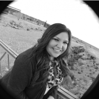 A black and white shot  looking through a black tube, of a young woman with long wavy dark hair standing against a railing and smiling, with a desert landscape in the background, wearing a dark blazer and a white silk scarf with a dot pattern.