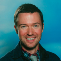 A close head shot of a young man with short brown hair smiling in front of a blue background, wearing a plaid shirt, a blue tie, and a black windbreaker.