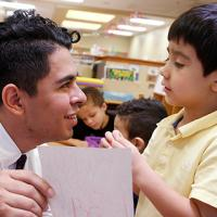 A close shot of a young male teacher with wild brown curly hair in a classroom, handing an art assignment back to an elementary school boy with short black hair.