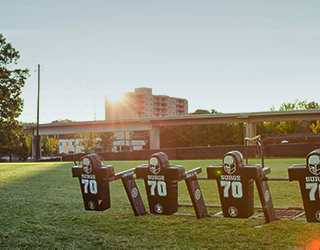 Green grassy football field, with football equipment in the foreground; a school building and blue sky in the background.